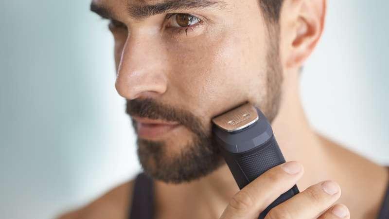 Мужчина использует триммер для бороды